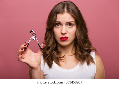 Beautiful young woman holding an eyelash curler