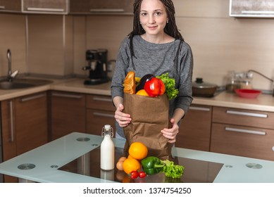 A beautiful young woman holding full paper bag with products in hands stands on the background of the kitchen. Healthy and fresh organic food for a balanced diet