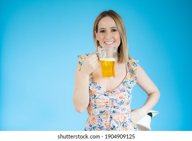 Beautiful young woman holding glass of beer over blue background.