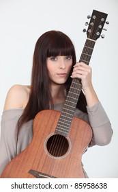 beautiful young woman holding a guitar
