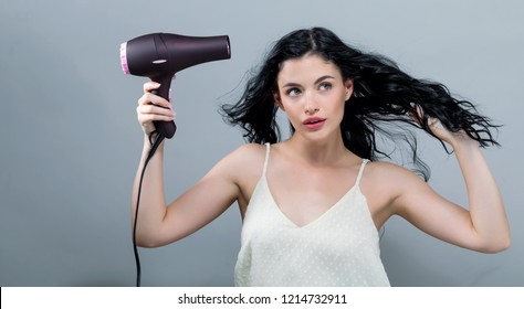 Beautiful young woman holding a hairdryer on a gray background