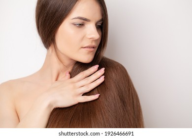 Beautiful young woman holding her healthy and shiny hair
