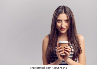 Beautiful young woman holding hot drink in disposable paper cup, isolated over gray background, with copy space