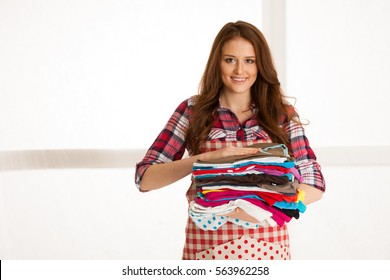 Beautiful young woman holding laundry  after she finished ironing