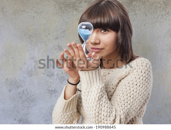 beautiful young woman holding and looking a sand clock