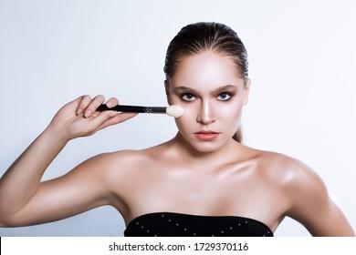 Beautiful young woman holding makeup brush near her face