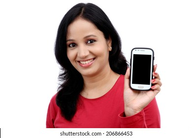 Beautiful young woman holding mobile phone against white background