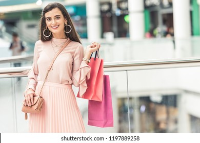 beautiful young woman holding paper bags and smiling at camera in shopping mall