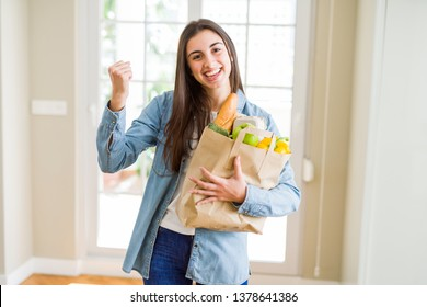 Beautiful young woman holding paper bag full of healthy groceries screaming proud and celebrating victory and success very excited, cheering emotion