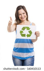 Beautiful young woman holding a paper card with the recycling symbol, isolated over white background