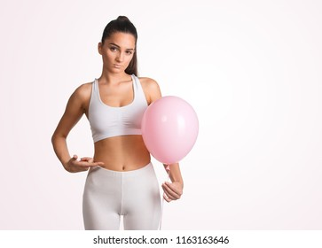 Beautiful young woman holding a pink balloon