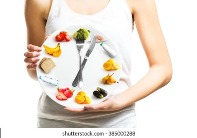 Beautiful young woman holding a plate with food, diet and time concept close up