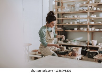 Beautiful young woman holding pottery instrument for scraping, smoothing, shaping and sculpting. Lady siting on bench with pottery wheel and making clay pot