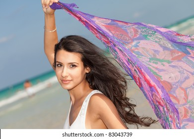 Beautiful young woman holding a purple shawl against the ocean breeze enjoying the South Beach shoreline in Miami.