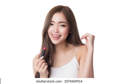 Beautiful young woman holding a red lipstick, isolated on white background