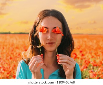 Beautiful young woman holding red poppies in front of her eyes and standing in flower meadow at sunset.