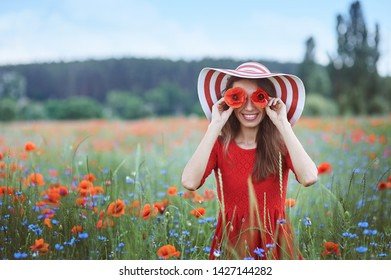 Beautiful young woman holding red poppies in front of her eyes and standing in flower meadow