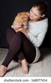 Beautiful young woman holding a red kitten, studio shot