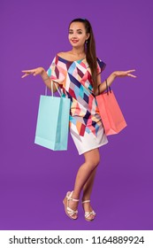 Beautiful young woman holding shopping bags and looking at the camera while standing against purple background.
