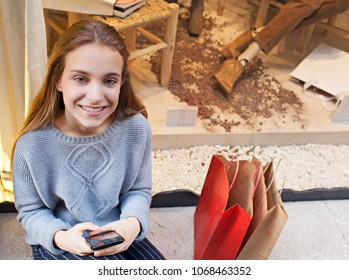 Beautiful young woman holding smart phone and shopping bags, looking smiling networking, sitting by store window, outdoors. Female teenager consumer using technology, leisure recreation lifestyle.