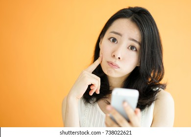 Beautiful young woman holding smart phone against orange background.