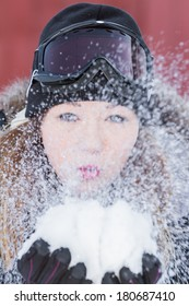 beautiful young woman holding snow in her hands and blowing it away with a slow shutter speed