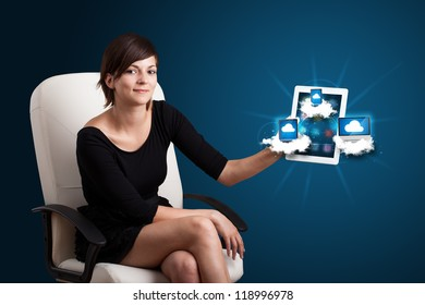 Beautiful young woman holding tablet with modern devices in clouds