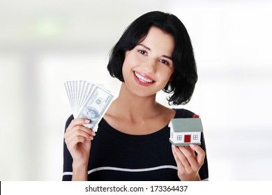Beautiful young woman holding US dollars bills and house model over white - real estate loan concept