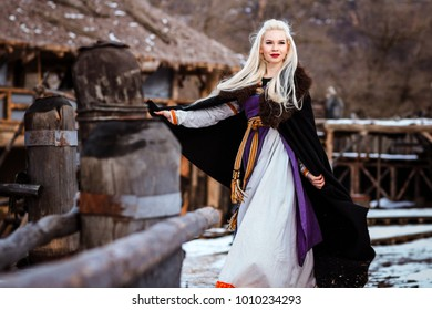 Beautiful young woman holding a viking with blond hair. Image of Historical figure