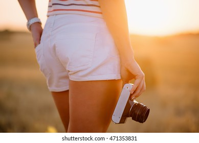 beautiful young woman holding a vintage camera at hip level, close-up, in the field at sunset