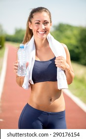 Beautiful young woman holding water bottle after jogging. Looking at camera.