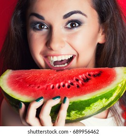 beautiful young woman holding watermelon against red background
