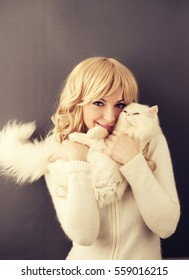 Beautiful young woman holding a white cat