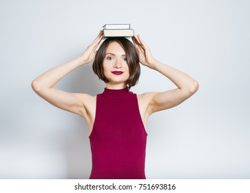 beautiful young woman holds books on her head, wearing a burgundy dress, isolated in studio on a gray background