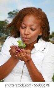 a beautiful young woman holds a green plant to represent earth friendly concepts