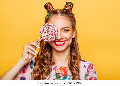 Beautiful young woman holds in hand candy