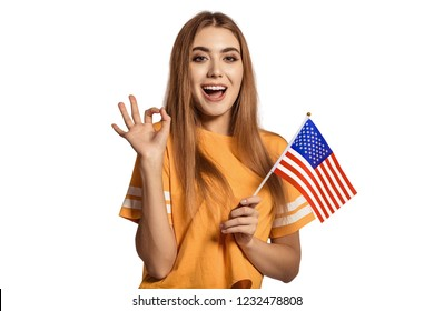 A beautiful young woman holds in her hands the flag of United States and shows the OK sign. Exchange student, learn English language. Tourist traveling. White background. Isolate. Football fan.