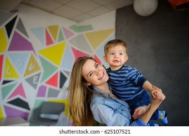 Beautiful young woman holds on hands of little son. Mother and the kid look in the camera and laugh.