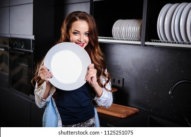 Beautiful young woman holds a white plate in a kitchen room, casual clothes, lifestyle portrait