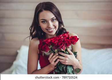 Beautiful young woman at home. Attractive girl is sitting on bed with red roses in hands. Saint Valentines Day.