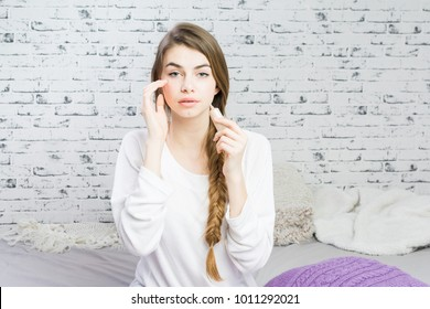 Beautiful young woman at home in bed applying makeup under eyes