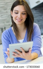 Beautiful young woman at home with digital tablet