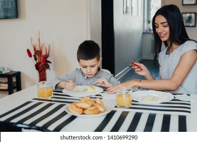 Beautiful young woman at home with her little cute son are having breakfast