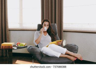 The beautiful young woman at home sitting on modern chair in front of window, relaxing in her living room, reading book and drinking coffee or tea