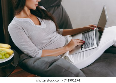 The beautiful young woman at home sitting on modern chair in front of window, relaxing in her living room and working with laptop