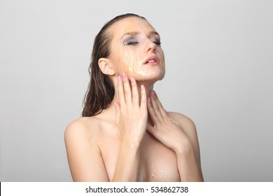 Beautiful young woman with honey on her face