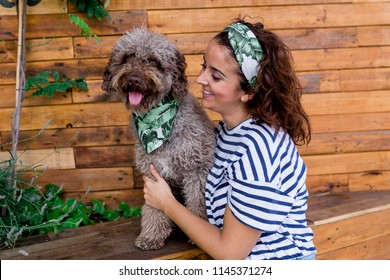Beautiful young woman hugging her dog, brown Spanish water dog over wood background. Daytime, love for animals concept and lifestyle. Dog wearing a green leaves bandana, woman wearing casual clothes