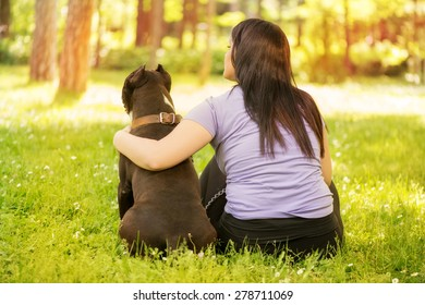 Beautiful young woman hugging her cute stafford terrier. They sitting on grass in the park and enjoying. Rear view.