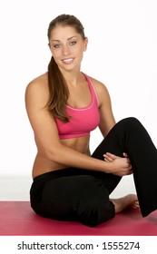 Beautiful Young Woman Hugging Leg at Gym