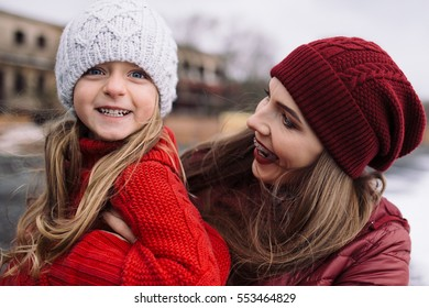 beautiful young woman hugging little girl. mother and daughter enjoy life outdoor